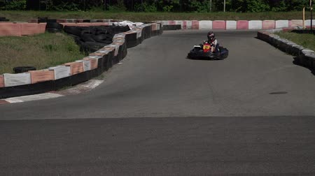 závodní dráha : Young racer at go-kart racetrack circuit championship crossing the finish line. Racer with a helmet competing on karting racetrack, fun youth activity