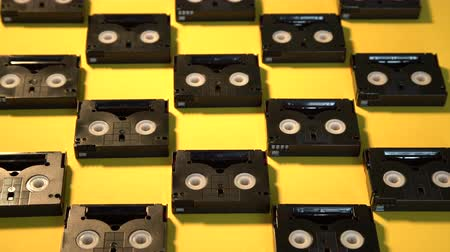 casette : Vintage mini DV cassette tapes used for filming back in a day. Pattern made of plastic video tapes on yellow background