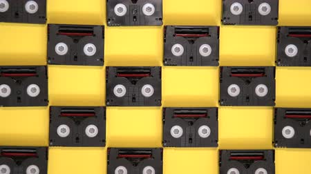gravador : Vintage mini DV cassette tapes used for filming back in a day. Pattern made of plastic video tapes on yellow background