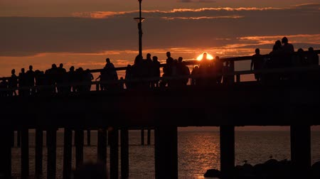 baltık denizi : People silhouettes walking along the pier at dramatic sunset on hot summer day in Palanga beach, Lithuania. Colourful sun setting into Baltic sea while tourists enjoying warm weather in popular resort