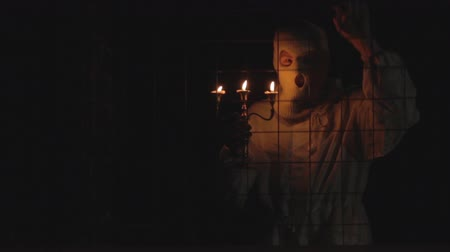 обряд : Unrecognizable man with scary halloween mask holding candles at night in the dark. Black magic ritual or scary halloween party performance