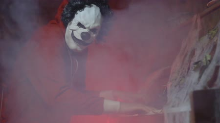 урод : Unrecognizable man with scary clown halloween mask playing piano with mystic fog and pumpkin in the background. Scary halloween party performance at night Стоковые видеозаписи