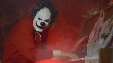 szörnyszülött : Unrecognizable man with scary clown halloween mask playing piano with mystic fog and pumpkin in the background. Scary halloween party performance at night Stock mozgókép