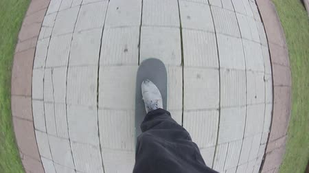 longboard : Point of view of skateboarder riding skateboard on the city sidewalk. Skater rolling freestyle in urban environment. Young man holding balance on board, extreme sport