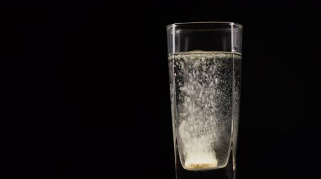 purificado : Vitamin C tablet dissolving in a glass of fresh mineral still water on dark backdrop. Bubbling pill in liquid with oxygen balls on black background Stock Footage