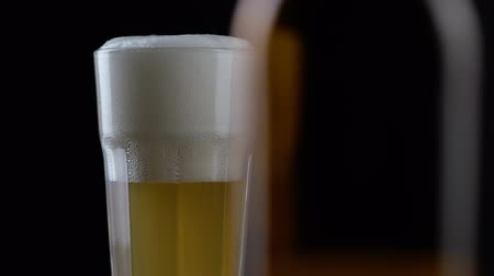 Октоберфест : Pouring fresh and cold craft beer into a glass with white foam on top on black background. Flowing foamy wheat or lager beer on dark background Стоковые видеозаписи