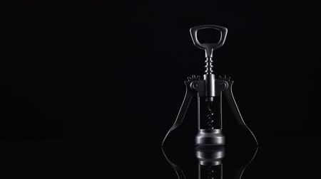 destapador : Silver colored bottle opener on black background. Universal shiny corkscrew tool with spiral for opening beverage drinks isolated on dark backdrop with space for text