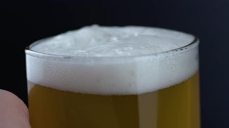 Октоберфест : Close up of fresh and cold craft beer in a glass with white foam on top on black background. Macro shot of flowing foamy wheat or lager beer on dark background