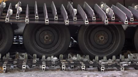 tracked : Caterpillar spikes on snowmobile in ski resort. Machine wheels with spikes for winter off road, extreme conditions. Tracked quad wheel, all terrain vehicle