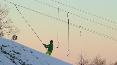 склон холма : Cables pulling skiers and snowboarders up the mountain in skiing resort. Sunset sky in the background