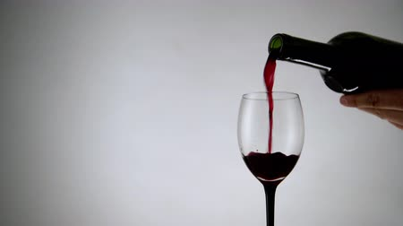 settings : Pouring red wine into a glass on white background. Wineglass full of alcohol drink on light backdrop