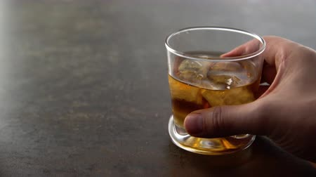 bourbon whisky : Man drinking glass of aged golden whiskey with ice cubes and putting it on the table. Hand putting amber colored alcohol beverage with rocks on rock background