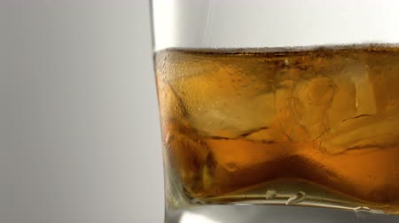 koktél : Glass of aged golden whiskey with ice cubes on the table. Amber colored alcohol beverage with rocks at the bar