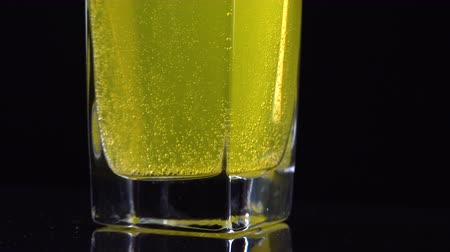 dissolução : Close up of vitamin C tablet dissolved in a glass of fresh mineral still water on dark backdrop. Macro shot of yellow bubbling liquid with oxygen balls Stock Footage