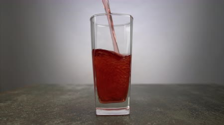 こぼれること : Grape juice pouring into a glass on light background. Fresh cocktail glass of red colored beverage on the table