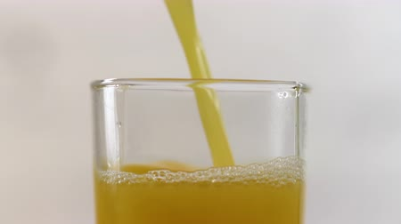 presleme : Freshly squeezed orange juice pouring into a glass on a table. Refreshing yellow beverage on white background Stok Video