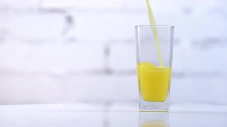 preslenmiş : Freshly squeezed orange juice pouring into a glass on a table. Refreshing yellow beverage on white background Stok Video