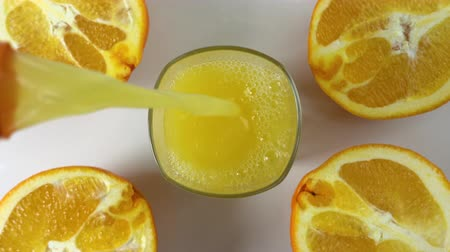 preslenmiş : Top view of freshly squeezed orange juice pouring into a glass on a table with slices of oranges next to it. Refreshing yellow beverage with fruits on white background