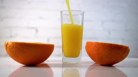 fructose : Freshly squeezed orange juice pouring into a glass on a table with slices of oranges next to it. Refreshing yellow beverage with fruits on white background