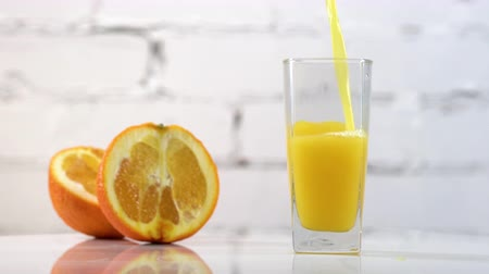 прессованный : Freshly squeezed orange juice pouring into a glass on a table with slices of oranges next to it. Refreshing yellow beverage with fruits on white background