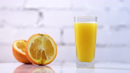 rodajas de naranja : Freshly squeezed orange juice in a glass on a table with slices of oranges next to it. Refreshing yellow beverage with fruits on white background Archivo de Video