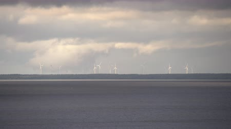obnovitelný : Windmills on the horizon with clouds in clear sky and sea in the foreground. Wind turbines, wind farms making electric power, green energy Dostupné videozáznamy