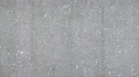 Snow flakes falling from the sky with building wall in the background, space for text. Winter backdrop with heavy snowfall
