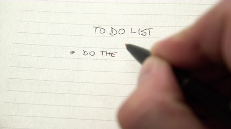 tick : Human hand writing tasks on to do list, chore checklist in notebook