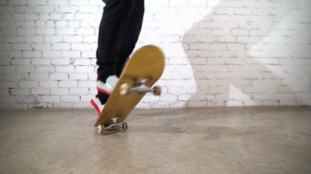 Skateboarder performing skateboard trick - 360 pop shuv it on concrete. Athlete practicing jump on white background, preparing for competition. Extreme sport Стоковые видеозаписи