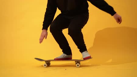 Skateboarder performing skateboard trick - pop shuv it on concrete. Athlete practicing jump on yellow background, preparing for competition
