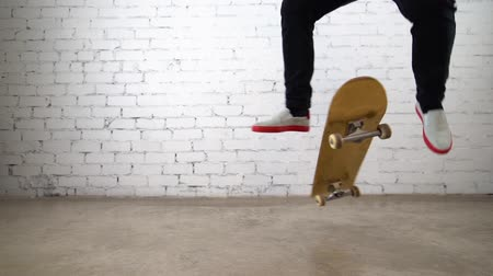 Skateboarder performing skateboard trick - pop shuv it on concrete. Athlete practicing jump on white background, preparing for competition