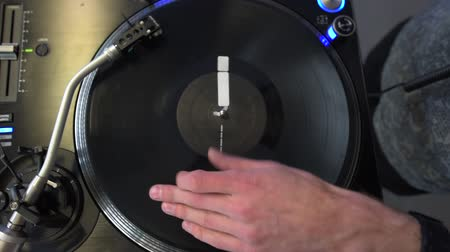 Professional DJ mixing analog vinyl record at the production studio. Entertainers hand spinning round music record at the party