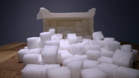 sweetener : Macro dolly shot of gliding through sugar cubes next into carton box on wooden table. Unhealthy food sweetener, sweet crystal cubes