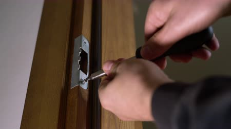 locksmith : Carpenter repairing door lock. Installing a door handle. Handyman tightening door hinge. Hands of the repairman with a screwdriver. Locksmith screwing bolt into wooden door