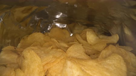 emballages : Dolly shot of camera sliding inside the potato chips bag. Opened pack of original taste delicious potato crisps. Fast food and unhealthy eating concept Vidéos Libres De Droits
