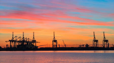 Container seaport terminal near the beach during sunset with dramatic colorful sky. Day to night time lapse.