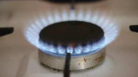 Closeup of a blue flame coming out of a vintage natural gas stove burner.