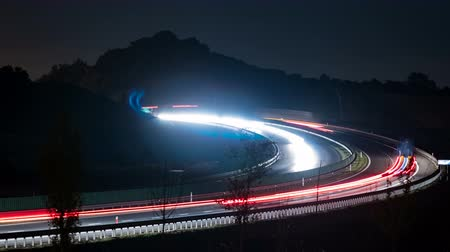 Light trails of cars driving fast on a highway bend at night time lapse.