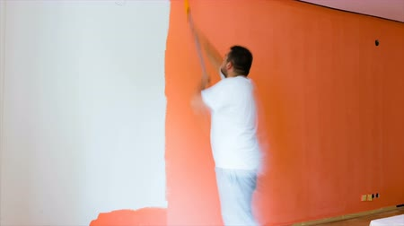 Young man painting home interior wall while renovating house time lapse. Vídeos