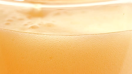 Close up on a lager beer with dense foam bubbles moving in a glass. Vídeos