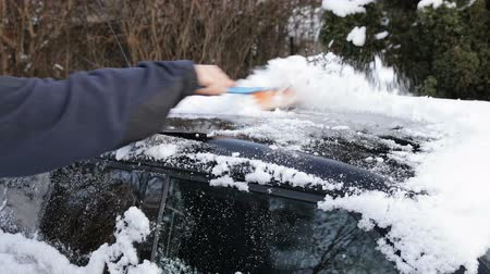 Young man cleaning snow from his car with a brush.