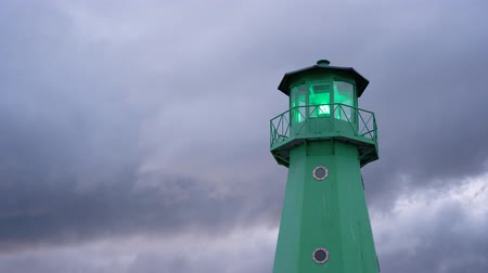Green lighthouse flashing light against dramatic sky time lapse.