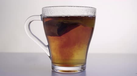 Brewing tea - pouring hot water in a translucent cup. Vídeos