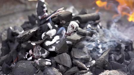 Black charcoal burning with smoke and fire in a barbecue grill in slow motion. Delicious meal preparation.