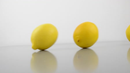 lemons rolling down a tilted table down a tilted table with white background Dostupné videozáznamy