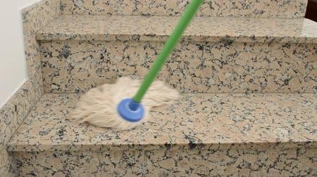 close up of a mop cleaning a staircase