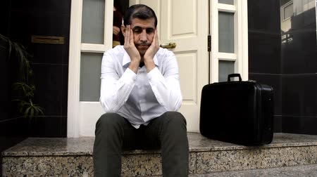 divórcio : man expelled of home sitting and weeping and the wife holding the suitcase of husband in background at the doorway as concept of divorce Stock Footage