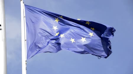 waving the europe flag with blue sky in background in sunny day