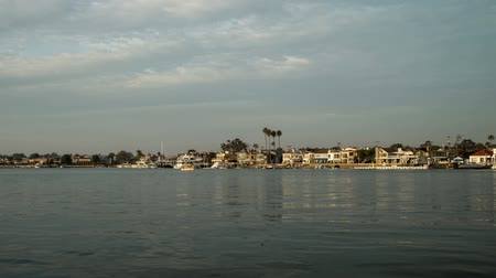 Time lapse video of the historic Balboa Island Ferry connecting visitors from Balboa Island to The Balboa peninsula. Clip includes fast moving boats and clouds.
