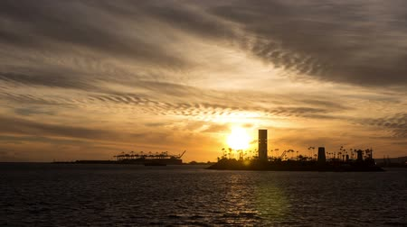 Time lapse video shows sun setting behind off shore THUMS off shore oil islands in Long Beach, California Wideo